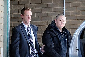 De Jun 'Kevin' Zheng is led away by police.