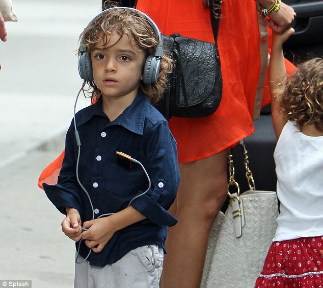 Music on his mind: The couple's cute son Levi was seen listening to his iPod while wearing large headphones over his tousled hair