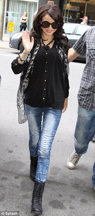 Black on black: The petite starlet donned a black shirt and leather boots with acid wash jeans