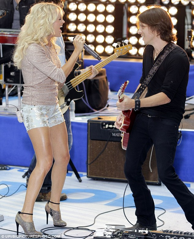 Legs on show: Underwood rocks out with a member of her band in front of a packed out crowd