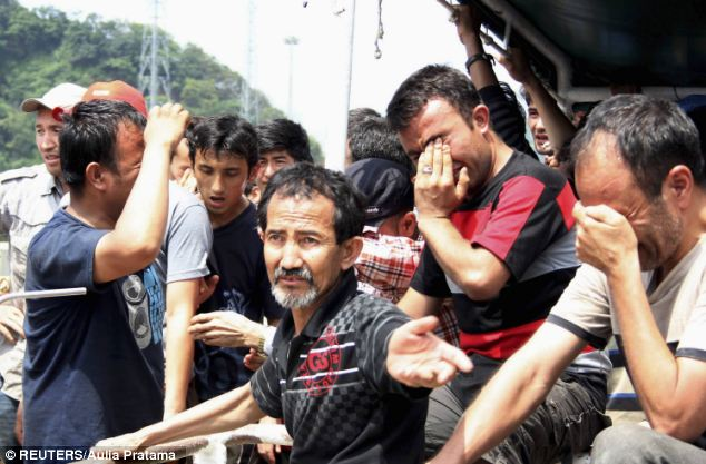 Reduced to tears: Asylum seekers from Afghanistan, Iraq and Iran had to be rescued after their wooden boat began to sink off the coast of Indonesia in April