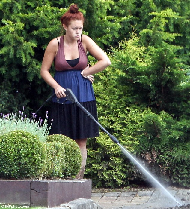 Worn out: Lacey Turner looked tired out as she carried out a spot of power-washing in her garden