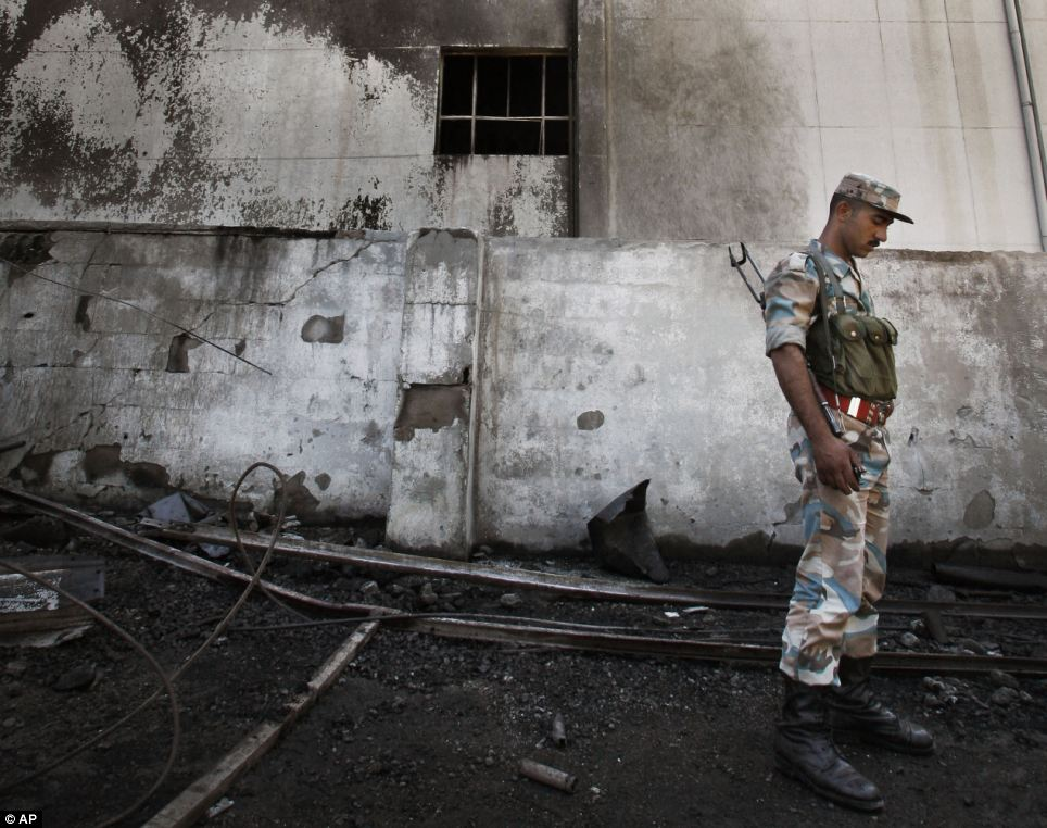 War-torn: A Syrian soldier investigates the scene after the explosion