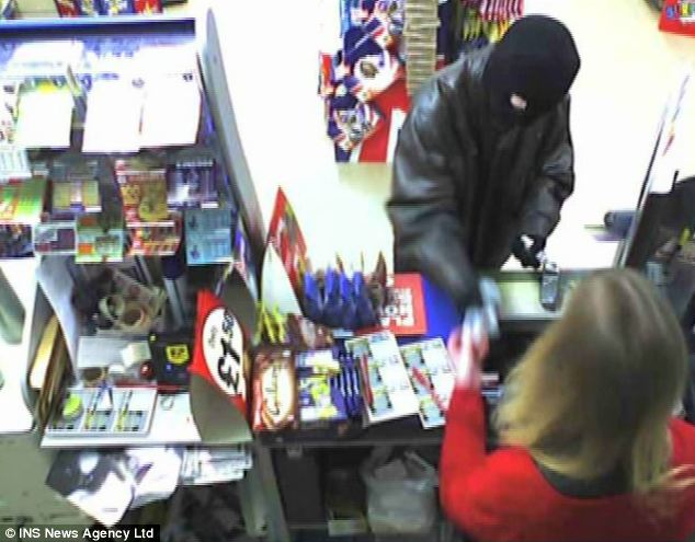 Allan demands cash from the woman behind the till: He doesn't take very much of it though