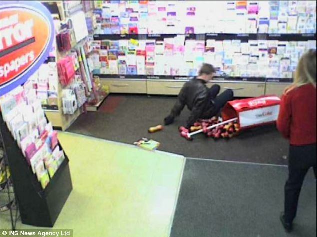 What a plonker! Allan topples backwards into a drinks display after failing to get out of the door