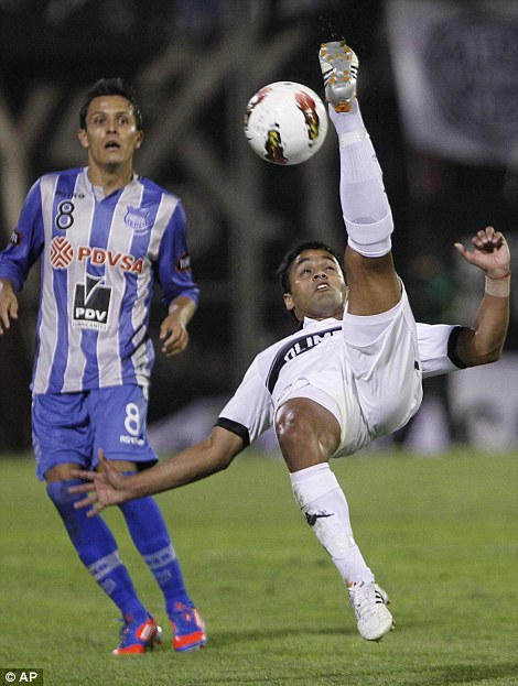 Football crazy: Olimpia's Sergio Ariosa (left) performs an overhead kick as Real Madrid boss Jose Mourinho (right) adjusts his microphone