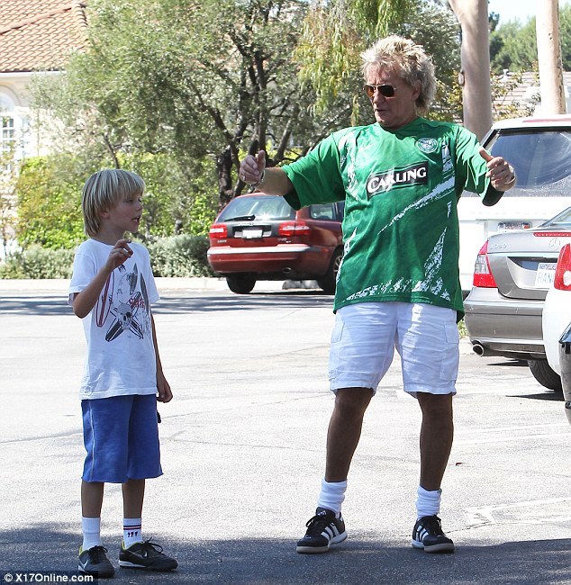 Young at heart: The 67-year-old was seen entertaining young son Alastair while wearing a football shirt and shorts