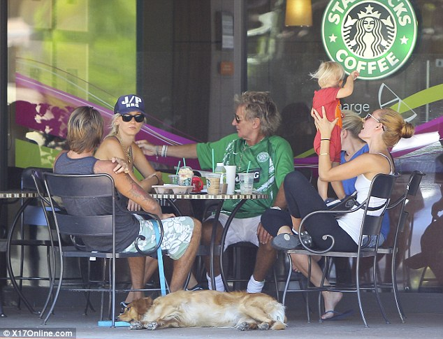 Taking it easy: The Stewart entourage chatted amongst themselves in the LA sun as they enjoyed a coffee outside