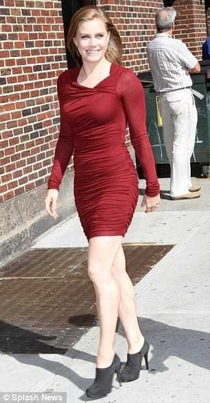 Hot to trot: Amy teamed the red dress with a pair of black suede boots as she strutted down the street