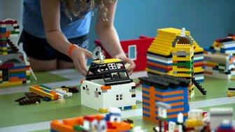 A woman builds a Lego house