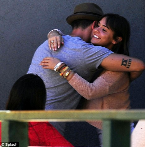 Bear hug: The 33-year-old stud, who's engaged to actress Cara Santana, flaunted his defined biceps in a grey t-shirt as he briefly visited with the grinning ladies