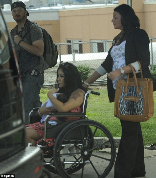 Protective mother: Snooki was spotted leaving the hospital in a wheelchair while clutching on to her baby son Lorenzo