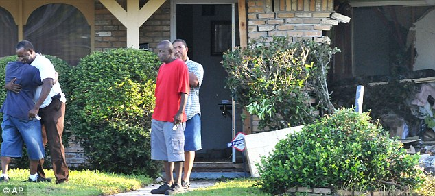 Grief: A man, possibly her father Gerald, is comforted outside the family home where Miss Jackson lived with her parents while she attended Wolfson High School