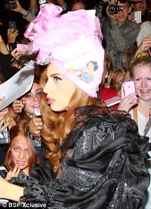 New favourite look: The singer sported brunette hair and the pink turban earlier on in the evening as she signed autographs