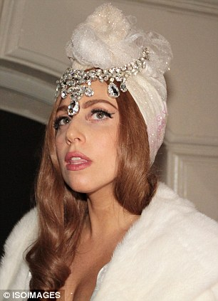 New look: Gaga modelled a glittery turban which she teamed with a jewelled headpiece