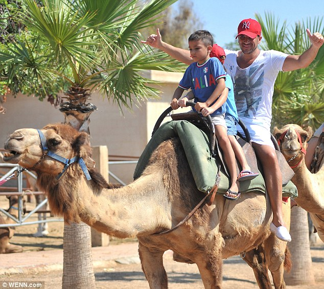 Welcome to the jungle: The father-of-two was in good spirits as he and his son jumped on  camel for a ride