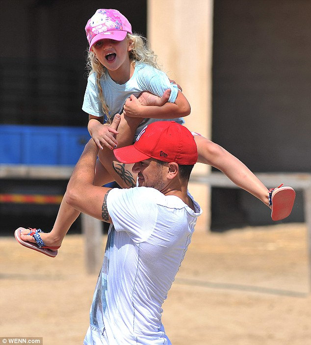 Showing off his strength: The 39-year-old had his daughter in hysterics as he lifted her in the air
