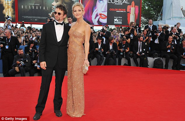 Taking centre stage: Kate and her rocker fiancé seemed happy to pose for photographers on the carpet