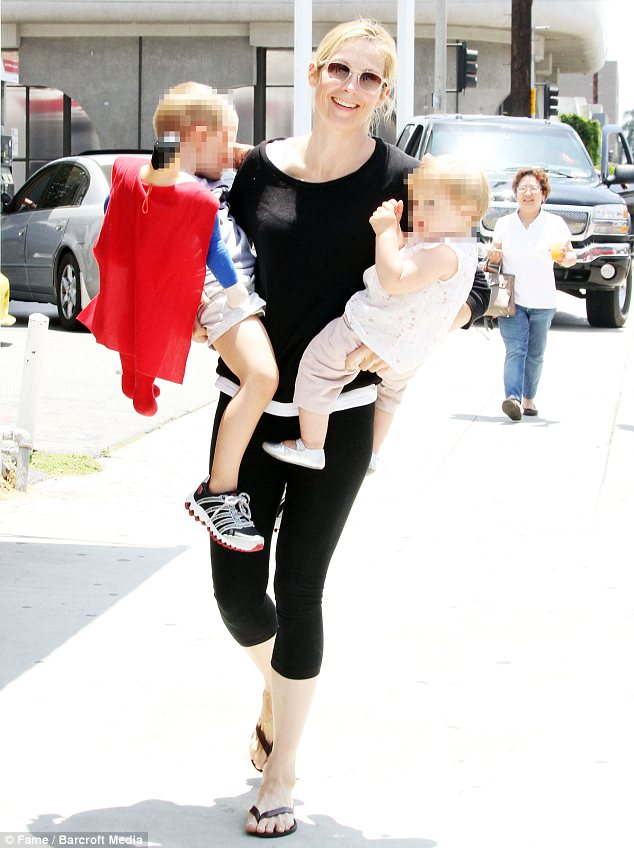 Working mom: Rutherford was all smiles in June 2010 when out and about with her brood