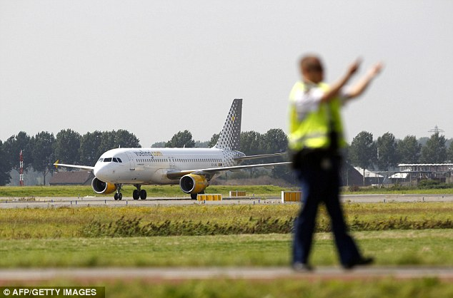Stand back: A security guard directs traffic away from the plane, which had 180 passengers on board, after it landed a mile from the main terminal