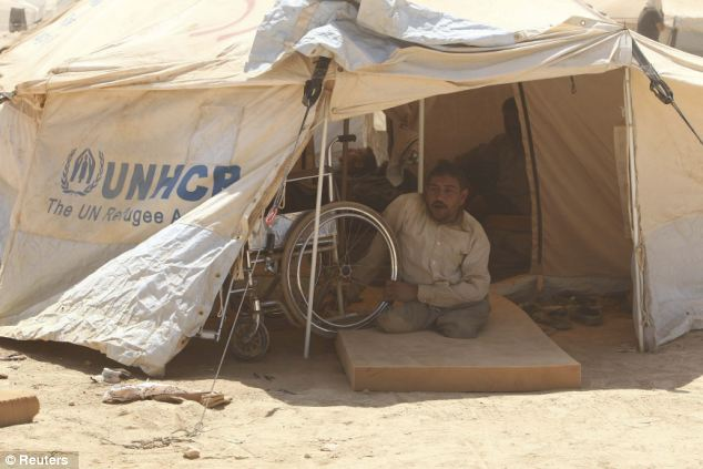 Humanitarian crisis: A handicapped Syrian refugee looks out of his tent at the Al Zaatri refugee camp in the Jordanian city of Mafraq. The camp is one of many set up along the 53-mile border between Jordan and Syria