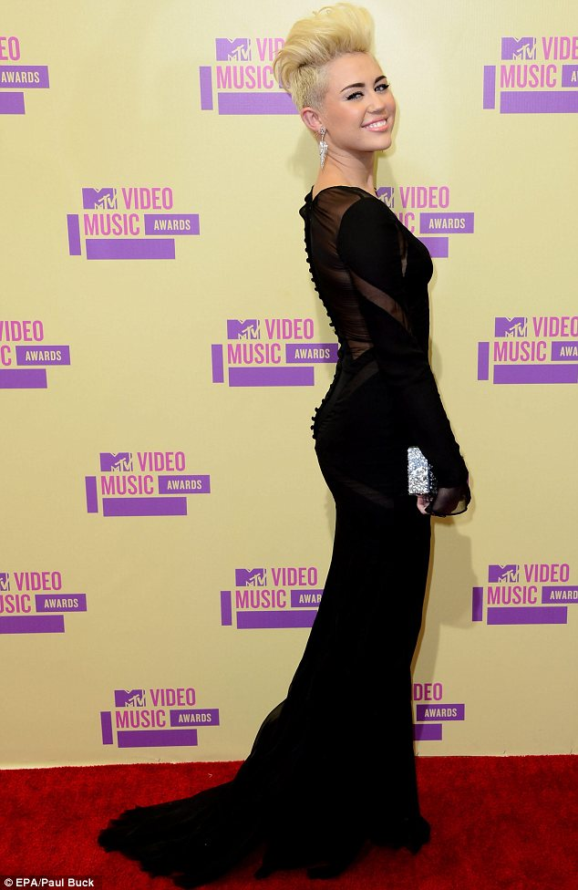 Feisty: Miley teamed the racy gown with plenty of attitude and eyebrow pencil in equal amounts