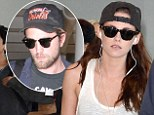 Kristen Stewart jets out of Toronto in Robert Pattinson's baseball cap... after claiming they are 'totally fine'