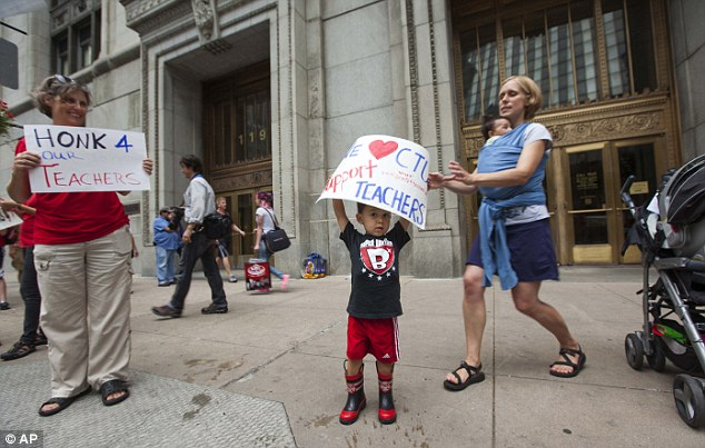Helping hand: A mother rushes to help a young boy hold up a sign on Friday expressing his support for the city's teachers