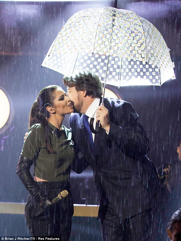 Singing in the rain: Cheryl was congratulated after the wet routine by Jonathan, who took cover under an umbrella