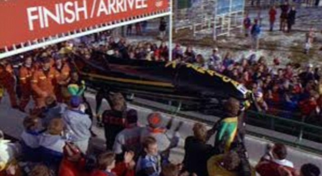 To the sounds of cheers the Jamaican bobsleigh team carry their sled across the finish line in the film Cool Runnings, based on the story of the 1988 Winter Olympics team