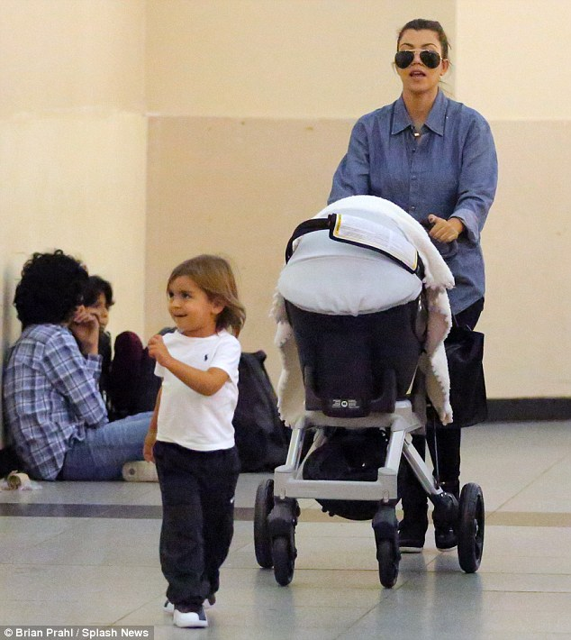 On their way: Tiny Penelope was seen snuggled up in her stroller as her mother pushed her through JFK airport last night, alongside her son Mason, two