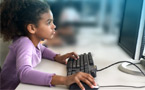 Picture of a young girl working on a computer in an elementary school computer lab