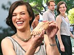 That'll get your attention! Milla Jovovich holds up a severed foot prop as she chats with Extra television host Mario Lopez in West Hollywood on Wednesday