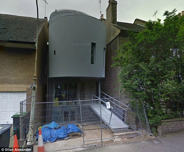 Unfinished: The sleek home remains surrounded by steel fencing and tarpaulin six years after construction started