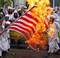 Fury: Muslim men in Bangladesh burned an American flag during protests against an anti-Mohammed film on Thursday
