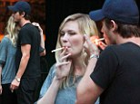 You light up my life: Kirsten Dunst and Garrett Hedlund share a cuddle on a cigarette break