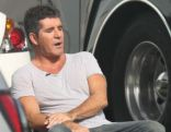 Simon Cowell enjoys a much deserved cigarette break after posing for pictures with fans on the set of his TV show in Miami