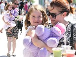 Balancing act! Alyson Hannigan juggles her daughter Satyana with a tray of cool drinks ... and a purple hippopotamus