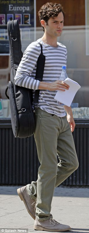 Music man: Penn Badgley was also spotted on set today, dressed casually with a guitar slung over one shoulder