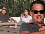 Actor Tom Hanks and wife Rita Wilson enjoy the sunny Malibu weather drinking beer and white wine outside their Malibu front beach mansion