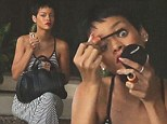 No diva behaviour here! Rihanna touches up her own make-up as she waits patiently for a ride to go and pick up some fast food