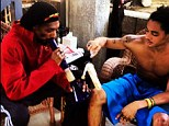 Smoking: Snoop Dogg's son Corde Calvin Broadus apparently lights his bong for him in this image he posted on Twitter