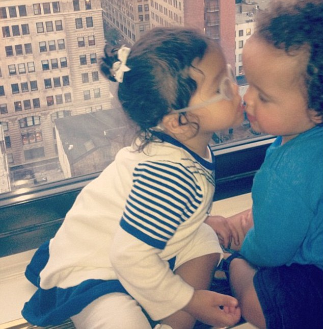 Sibling love: Monroe gives her twin brother Moroccan a kiss in a [icture tweeted by their mother Mariah Carey