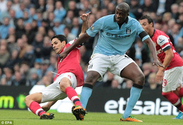Midfield battle: Arsenal's Mikel Arteta goes to ground under pressure from Manchester City's Yaya Toure