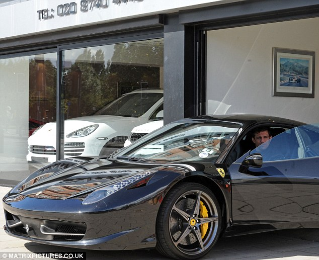 Eyeing up the models: The star puts his love woes aside to look at new motors in West London on Tuesday