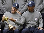 Looking for the Midas touch: Love (left) and Woods get their hands on the trophy on Tuesday