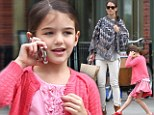 Is that Tom on the line? Suri Cruise lights up and does some dance moves as she chats away on Katie Holmes's cell phone