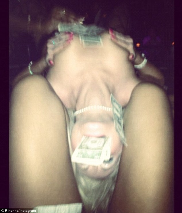 Making it rain: A topless stripper was covered in money as she stuck her head between Rihanna's thighs