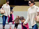 Make ours a babyccino!: Suri Cruise holds hands with a new friend as stylish duo hit Starbucks for a playdate with Katie Holmes