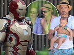 A stark contrast!: Robert Downey Jr. suits up on the Iron Man 3 set after some R&R poolside with the family